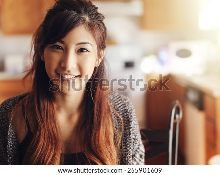 happy smiling asian teen girl portrait in kitchen - stock photo