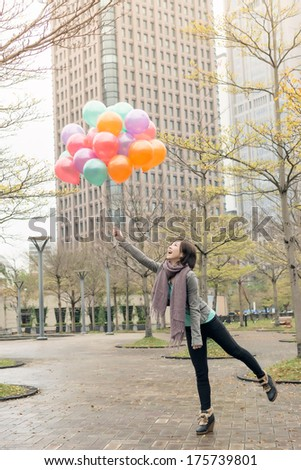 Happy smiling Asian woman holding balloons at street, Taipei, Taiwan, Asia. - stock photo