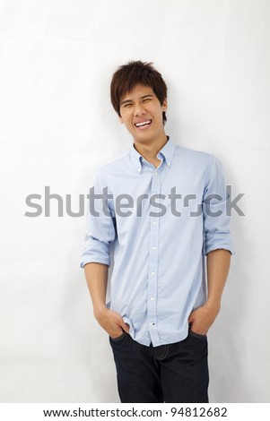 Happy smiling asian young man leaning against white wall - stock photo