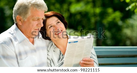 Happy smiling attractive senior couple reading together, outdoors, with copyspace - stock photo