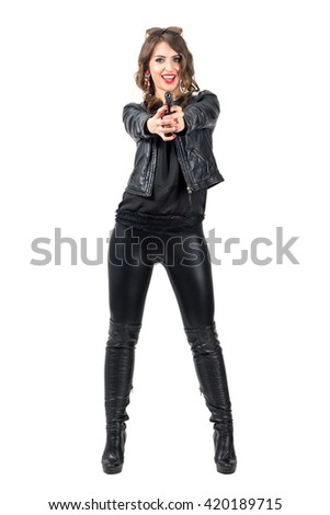 Happy smiling attractive woman in black leather pointing gun at camera. Full body length portrait isolated over white studio background.  - stock photo