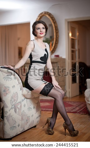 Happy smiling attractive woman wearing an elegant dress and black stockings sitting on the sofa arm. Beautiful young sensual female with short tight fit dress and high hills shoes leaning on couch