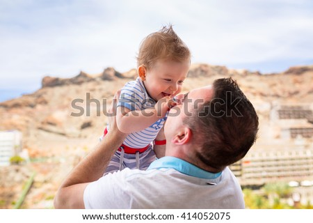 Happy smiling baby boy held up by his father on holidays - stock photo