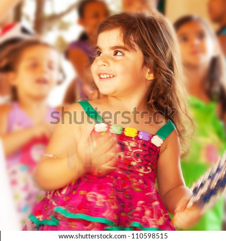 Happy smiling baby girl, adorable cheerful female child enjoying dance on carnival festival, sweet kid having fun on birthday party outdoor, pretty little girl portrait, happiness concept - stock photo