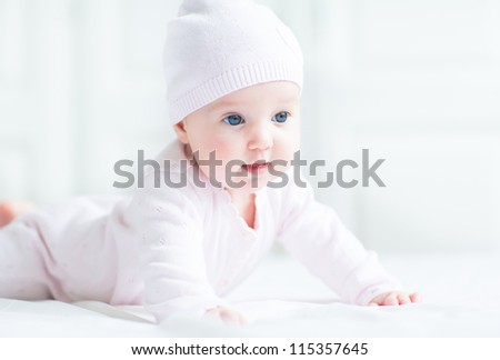 Happy smiling baby girl in a pink knitted hat - stock photo