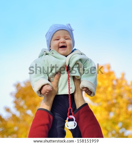 Happy smiling baby held up by his father against the sky. - stock photo