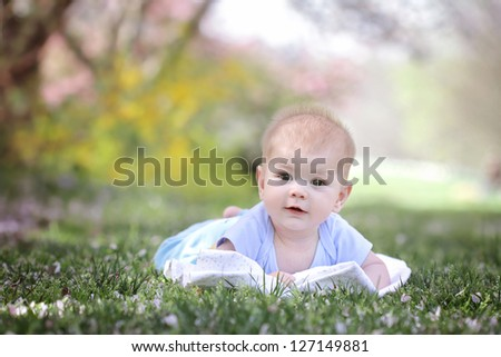 Happy smiling baby lying down in grass in a park - stock photo