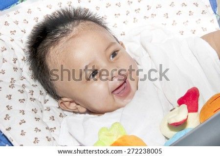 Happy smiling baby on a white cloth with a red bow. - stock photo