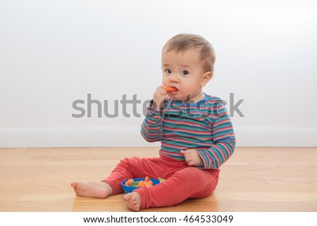 Happy, smiling baby playing with food, sitting on the floor with a white background. Ethnically ambiguous infant in bright clothing, eating carrots and broccoli from a blue bowl. Happy, healthy.