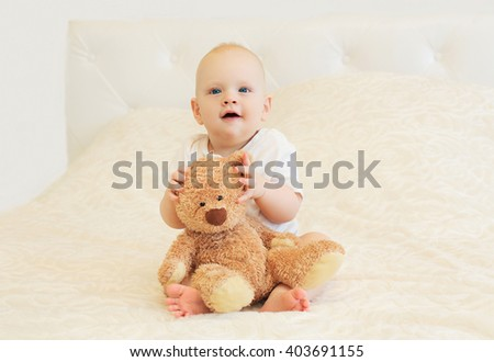 Happy smiling baby playing with teddy bear on bed at home - stock photo