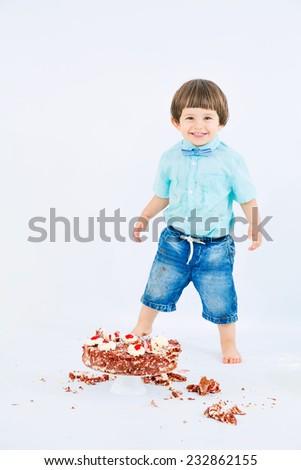 Happy smiling baby with smashed birthday cake, having fun - stock photo