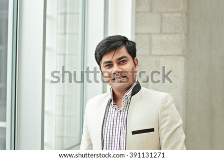 Happy smiling bangladesh business man standing indoor at the office