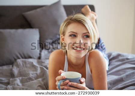 Happy smiling beautiful blond woman awaking with cup of coffee at bedroom - stock photo