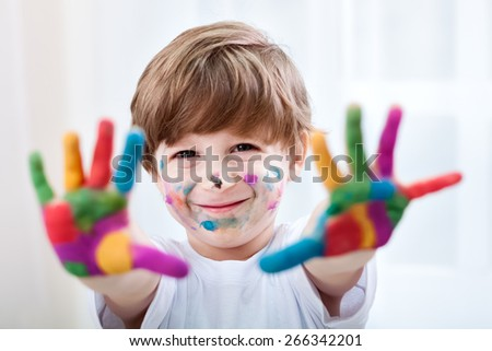 Happy smiling beautiful child playing with colors
