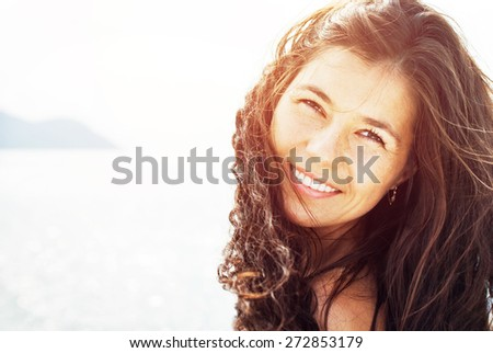 Happy Smiling Beautiful Woman with Black Curly Hair. On the Background of Sea in Sunlight - stock photo