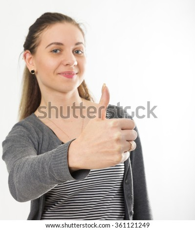 Happy smiling beautiful young brunette woman showing thumbs up gesture - stock photo