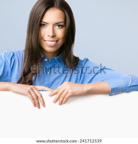 Happy smiling beautiful young business woman showing blank signboard with copyspace for text, over grey background - stock photo