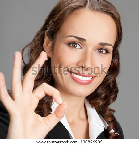 Happy smiling beautiful young business woman showing okay gesture, over gray background
