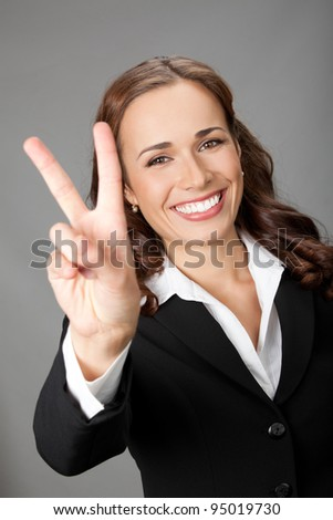 Happy smiling beautiful young business woman showing two fingers or victory gesture, over gray background