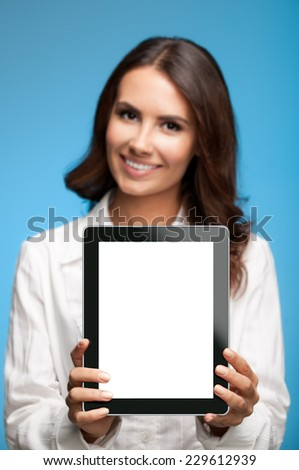 Happy smiling beautiful young businesswoman showing blank tablet pc for copyspace, against blue background - stock photo