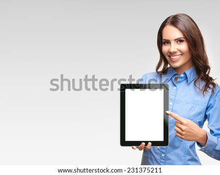 Happy smiling beautiful young businesswoman showing blank tablet pc monitor, against grey background, with copyspace area - stock photo