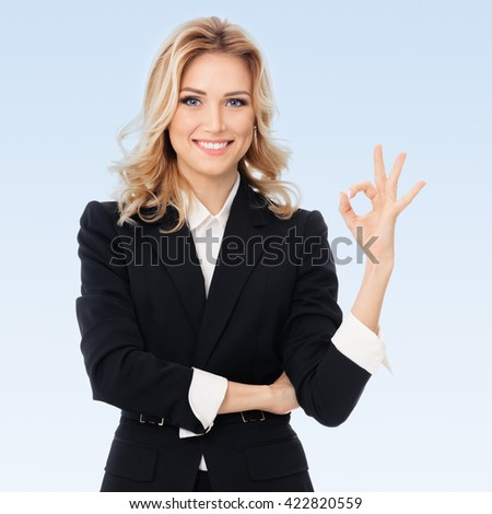 Happy smiling beautiful young businesswoman showing okay gesture, on blue background - stock photo