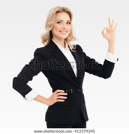 Happy smiling beautiful young businesswoman showing okay gesture, on grey background - stock photo