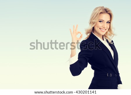 Happy smiling beautiful young businesswoman showing okay gesture, with blank copyspace area for text or slogan - stock photo