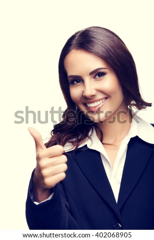 Happy smiling beautiful young businesswoman showing thumbs up gesture - stock photo