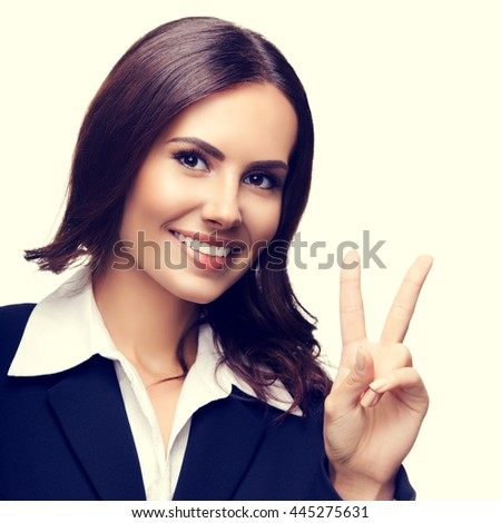 Happy smiling beautiful young businesswoman showing two fingers or victory gesture - stock photo