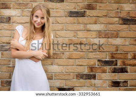 happy smiling blond girl near wall with copyspace background