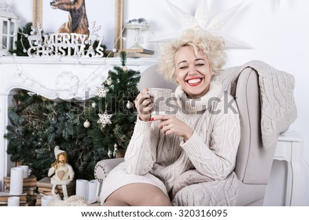 Happy smiling blonde lovely woman sitting in chair near fairplace and christmas tree. Series of winter holiday photos. Cozy home atmosphere - stock photo