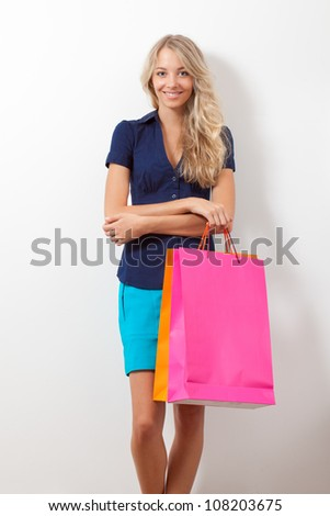 happy smiling blonde woman holding shopping bags over white wall - stock photo