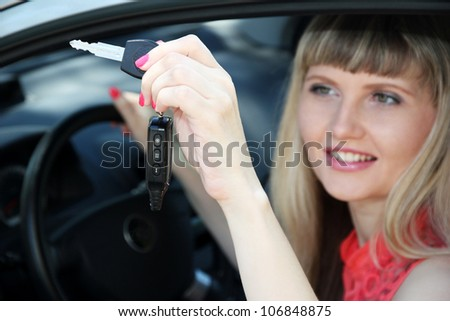 Happy smiling blonde woman in car - stock photo