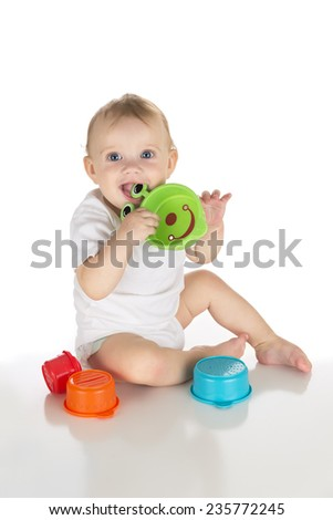 happy smiling blue eyed baby playing with educational cup toys over white background, motor skill development;  - stock photo