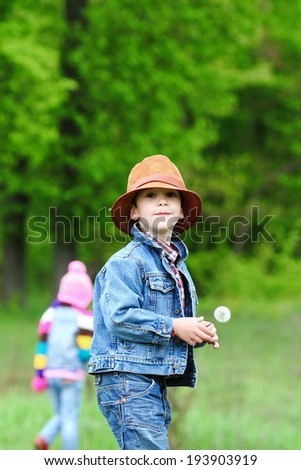 Happy smiling boy dressed in country style playing in the park near sunset with shallow depth of field and copy space to left and right