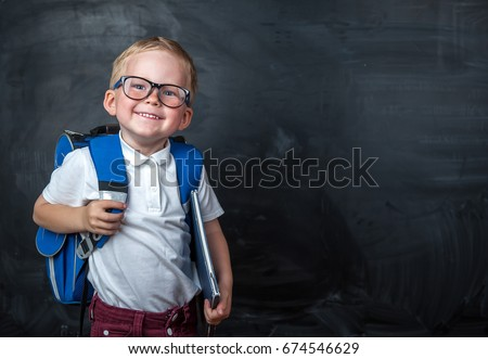 Happy smiling boy in glasses is going to school for the first time. Child with school bag and book in his hand. Kid indoors of the class room . Back to school.