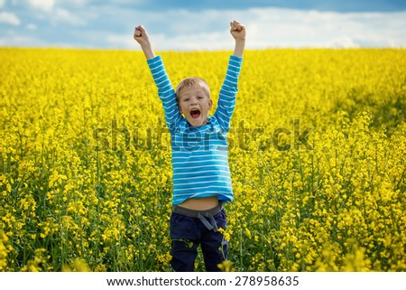 Happy smiling  boy jumping for joy on a yellow meadow in a sunny day - stock photo