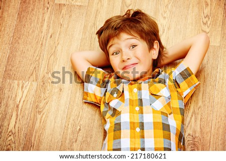 Happy smiling boy lying on a floor at home. Happy childhood. - stock photo
