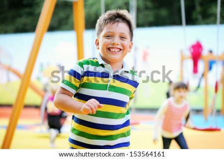 Happy smiling boy running on the playground