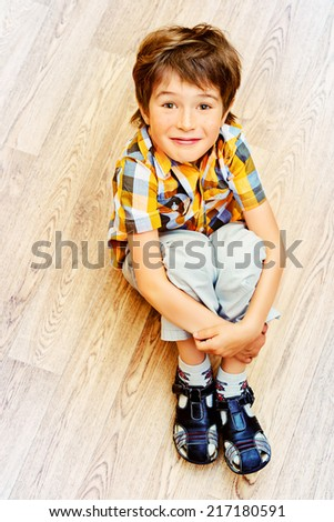 Happy smiling boy sitting on a floor at home. - stock photo
