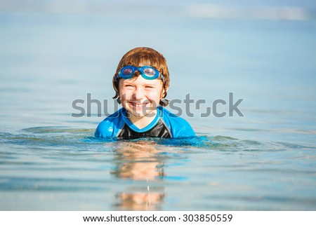 Happy smiling boy with goggles on swim in shallow water on sunny summer day - stock photo