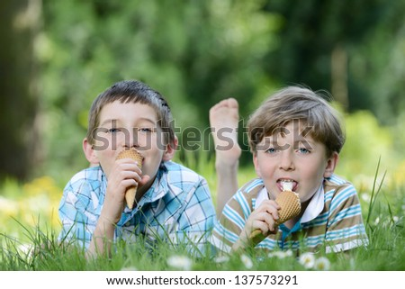 Happy smiling boys eat ice cream on a grass outdoors in spring park - stock photo