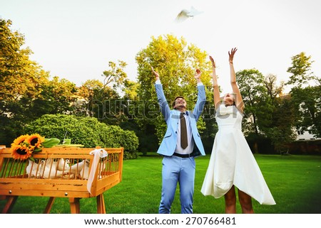 Happy smiling bride and groom hands releasing white doves on a sunny day - stock photo