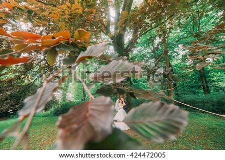 Happy smiling bride and groom in their wedding day near autumn tree - stock photo