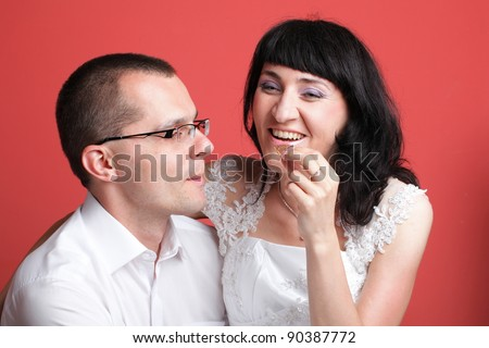 Happy smiling bride and groom young happy couple playfully eating cake on red background - stock photo