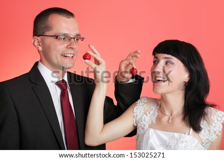 Happy smiling bride and groom young happy couple playfully eating strawberry on red background - stock photo