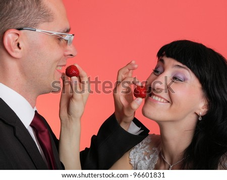 Happy smiling bride and groom young happy couple playfully eating strawbery on red background - stock photo