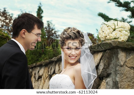 Happy smiling bride with groom outdoors leaning on stone wall with sky