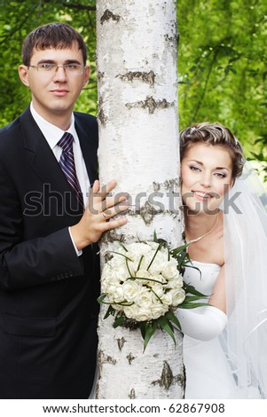 Happy smiling bride with groom outdoors next to birch tree with blurred green leaves